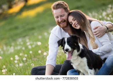 Romantic couple in love walking dogs in nature and smiling