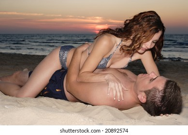 Romantic couple lying on a beach at sunset