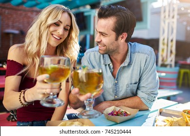 romantic couple making cheers with beer at outdoor mexican restaurant eating tacos