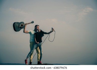 Romantic couple of musicians kissing on idyllic, blue sky. Cute girl or pretty woman, singer, with microphone and handsome man, guitarist, with guitar on sunny, summer day. Love to music, copy space