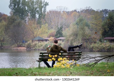 Romantic couple on a bench by the lake in autumn. Botanic garden in Chisinau.