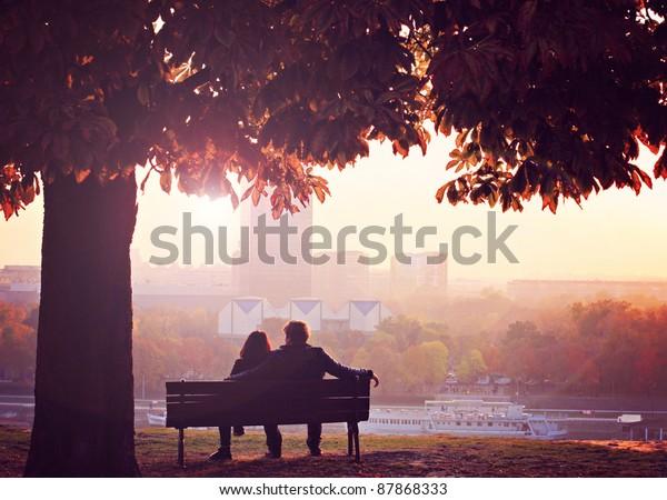 Романтическая пара на скамейке около тем Река