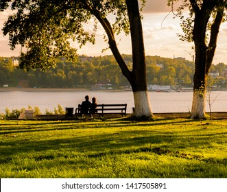 romantic couple on a bench in the rays of sunset on the banks of the Volga River. Kostroma.