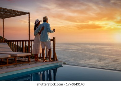 A romantic couple on summer vacation enjos the sunset over the mediterranean sea by the pool with a glass of Aperitif - Shutterstock ID 1776843140