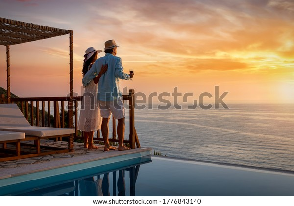 A romantic couple on summer vacation enjos the sunset over the mediterranean sea by the pool with a glass of Aperitif