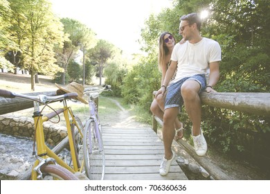 A romantic couple on wood bridge after walking with the bike around the park.Boy and girl rest after riding a bicycle in middle of the nature.friends who like spend free time doing outdoor activities