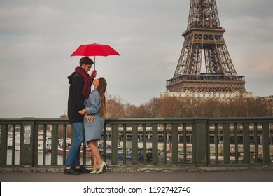 romantic couple in Paris near Eiffel tower in autumn, dating, man and woman kissing under umbrella