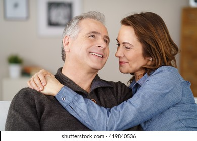 Romantic couple relaxing at home in an intimate embrace smiling with happiness as they share a tender moment