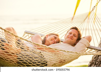 Romantic couple relaxing in tropical hammock at sunset