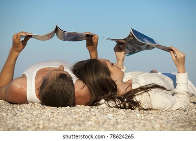 Romantic couple resting on beach and reading magazines