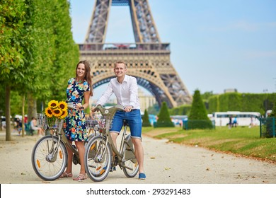 Romantic couple riding bicycles near the Eiffel tower in Paris