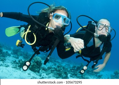 romantic couple scuba dive together in the ocean on a coral reef