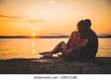 Romantic couple silhouettes on the beach, caressing each other with the sea and a beautiful colorful sunset in the background