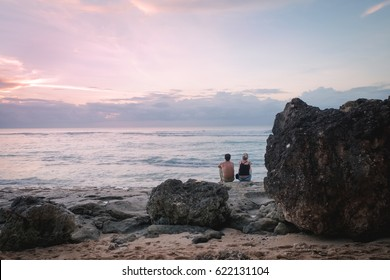 Romantic couple sit near rocks beach enjoy tender moments during sunset on horizon, outdoor Bali island landscape. Travel boyfriend and girlfriend relaxing together during summer vacation in Indonesia