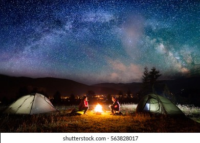 Romantic couple sitting at a campfire near tents in the night under incredibly beautiful starry sky and Milky way. Night camping