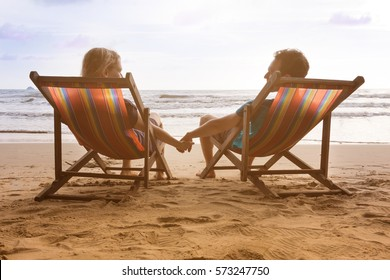 Romantic couple is sitting in deck chairs at beautiful sunset beach in Thailand and holding their hands while look each other. Happy romantic honeymoon vacation in tropical country