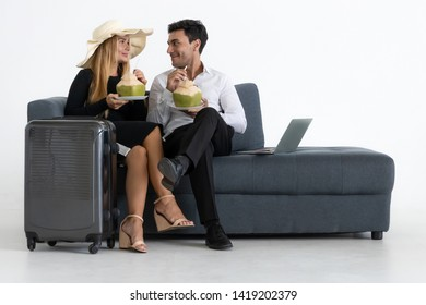 Romantic couple sitting and drinking coconut water on sofa. Summer vacation concept.