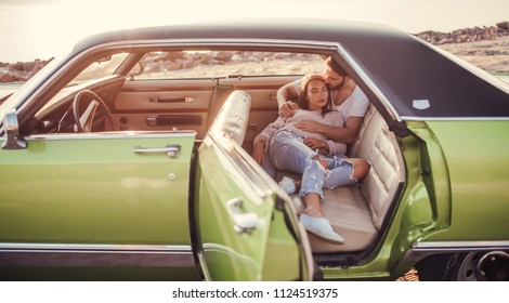 Romantic couple is sitting in green retro car on the beach.Handsome bearded man and attractive young woman in vintage classic car. Stylish love story.Hugging and kissing while being in car. Muscle car