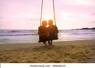 Romantic couple is sitting and kissing on sea beach on rope swing . Family vacation on honeymoon. Love and relationship