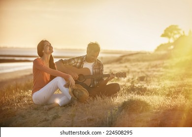 Romantic couple sitting on the beach at sunset with the man playing the guitar