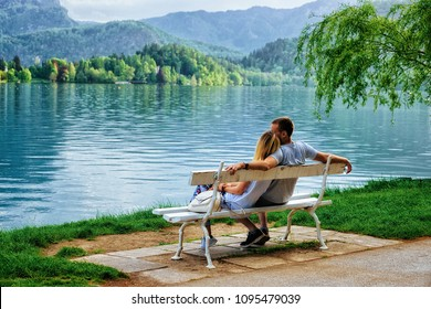 Romantic couple sitting on the bench at Bled Lake, Slovenia