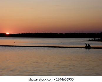 Romantic couple sitting on the pier on the midsummer night in Karujärve, Saaremaa, Estonia.