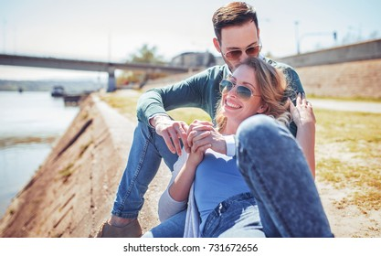 Romantic couple sitting on the riverside and enjoying in moments of love and tenderness. Dating, romance, lifestyle concept