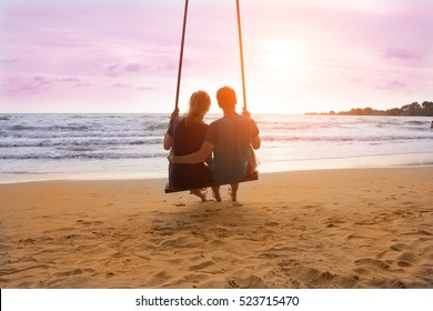 Romantic couple is sitting on sea beach on rope swing and looking at sunset horizon. Family vacation on honeymoon