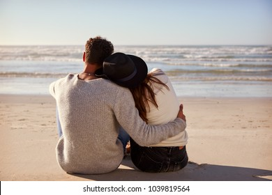 Romantic Couple Sitting On Winter Beach Together