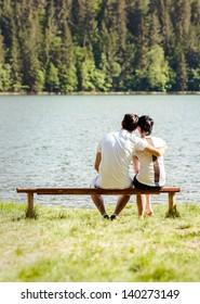 Romantic couple sitting on wooden bench near big lake