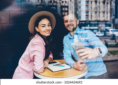 Romantic couple sitting at table in cafe during date posing for selfie on smartphone camera, hipster guy resting together with girlfriend using telephone for making picture for share in networks