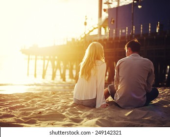 romantic couple sitting together by the beach with sunset