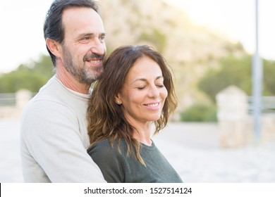 Romantic couple smiling,  cuddling and hugging on a sunny day