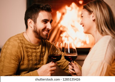 Romantic couple smiling and enjoying a drink, having a glass of wine by the fireplace