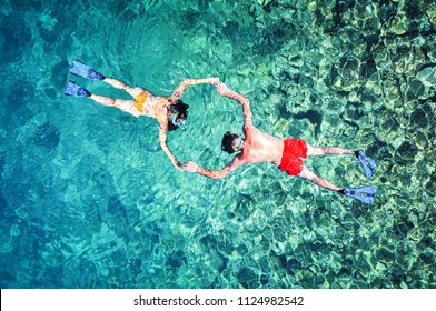 Romantic couple snorkeling in the sea. Drone shot