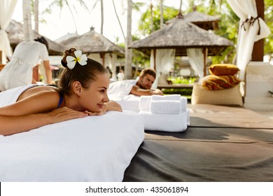 Romantic Couple Spa. Closeup Of Beautiful Healthy Happy Smiling Woman, Handsome Man Relaxing At Day Spa Resort. People Enjoying Body Relaxation Massage Outdoors In Summer. Relax Treatment Concept