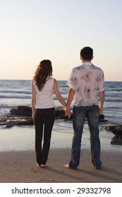 Romantic couple standing hand in hand at seaside