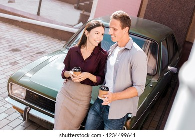 Romantic couple is standing near green retro car on the europian city street. Handsome caucasian man and attractive asian woman with vintage classic car. Love story of travallers in eurotrip