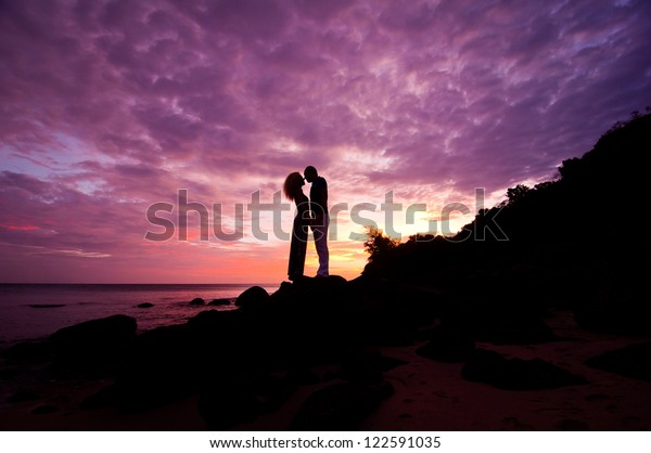 romantic couple standing on rocks by sea on purple dramatic sunset background