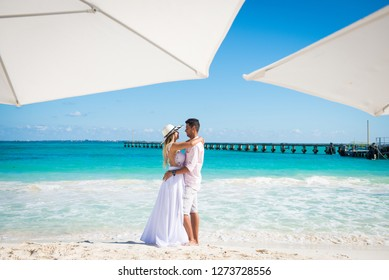 Romantic couple staying facing each other and hugging. White umbrelas at the first plan, and turquoise water on a background Vacation in Cancun.