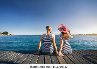 Romantic couple in striped dress sitting on pier and looking at blue Lake Issyk Kul in Kyrgyzstan. Summer and Sea concept.