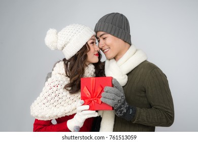 Romantic couple in a sweaters with red gift box