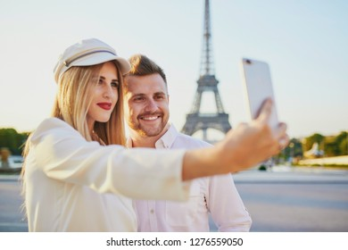 Romantic couple taking selfie near the Eiffel tower. Tourists in Paris enjoying the city