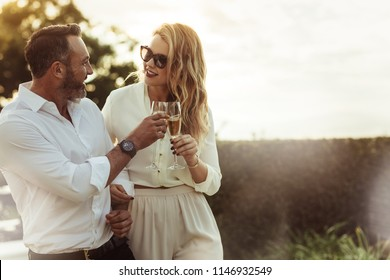 Romantic couple toasting wine glasses outdoors. Beautiful woman clinking wine glass with her boyfriend.