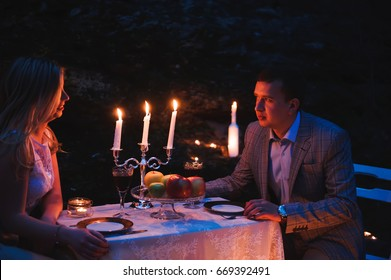 Romantic couple together over candlelight during romantic dinner outdoors