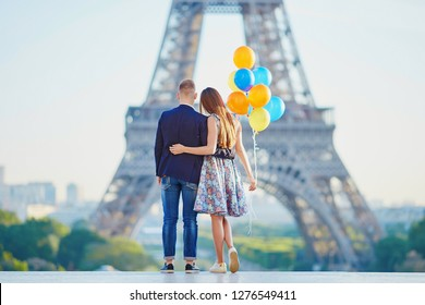 Romantic couple together in Paris with bunch of colorful balloons looking at the Eiffel tower