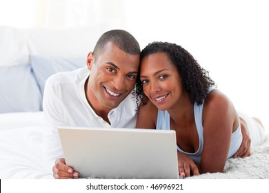 Romantic couple using a laptop lying on their bed