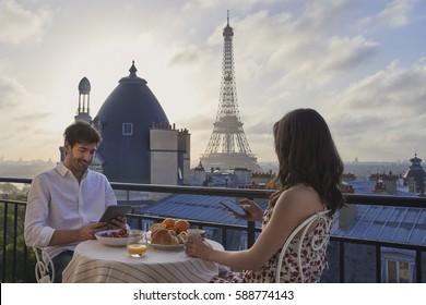 Romantic couple using technology digital tablet smart phone hotel breakfast terrace honeymoon Eiffel Tower Paris destination city of love