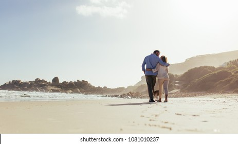 Romantic couple walking along the beach with a dog. Loving mature couple strolling on sea shore with dog.