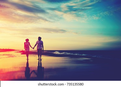 Romantic couple walking at the beach at sunset spending their honeymoon at vacations